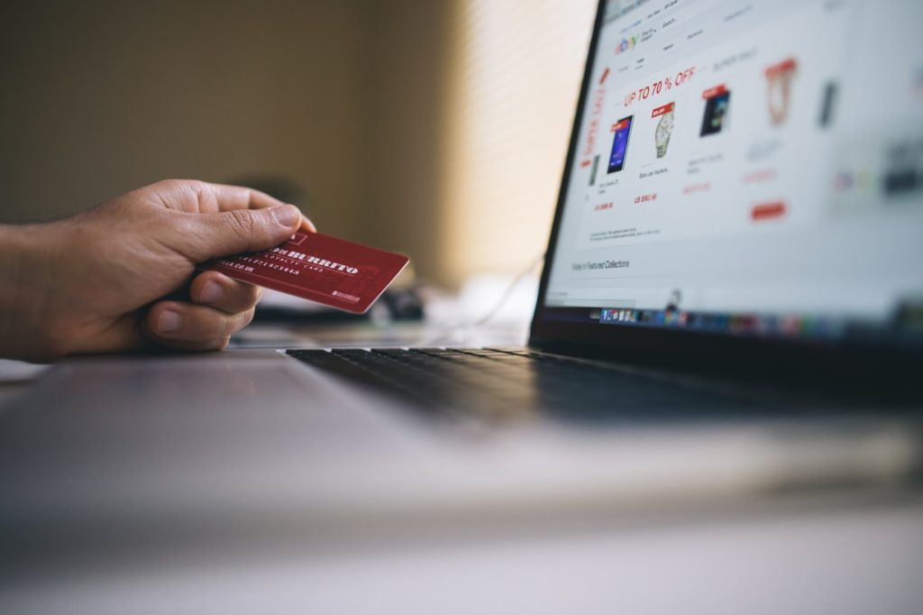 Person holding a credit card near a laptop