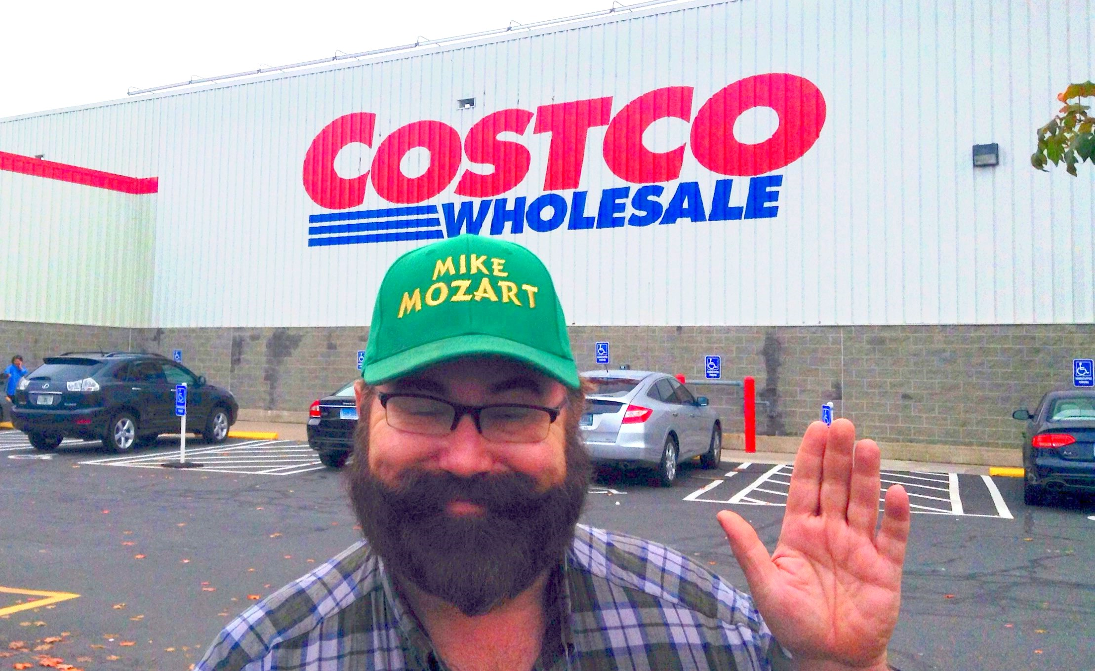 man with green cap near at the costco wholesale logo